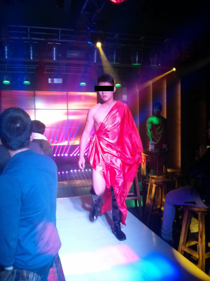A man in a Roman toga walks up the catwalk at Nono bar