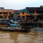Dredging operation: a digger on two floaters, prevented from floating away by a boat