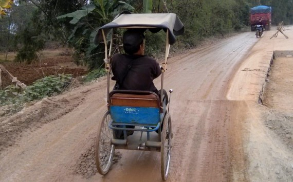 A handicapped man in his tricycle that is operated by jerking the steering wheel back and forth