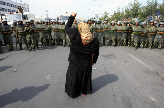 Uyghur woman facing a police cordon during protests in Xinjiang in 2009